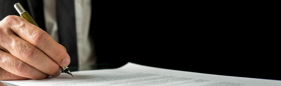 Businessman signing a document or contract in the office, close up horizontal banner format of his hand and the paperwork with copyspace.